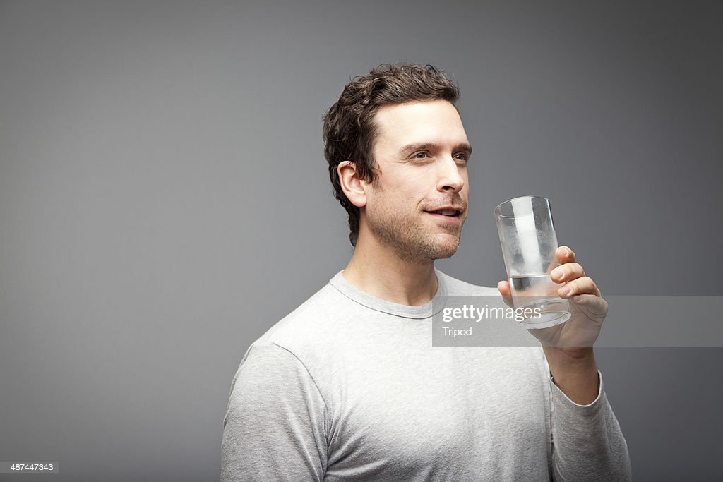 Man holding glass of water, smiling