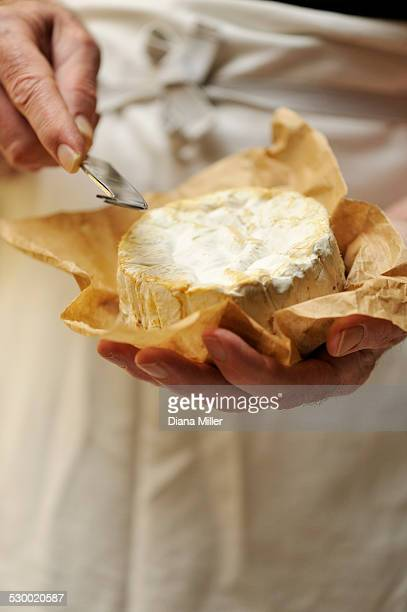 Man holding goats cheese and cheese knife, focus on hands