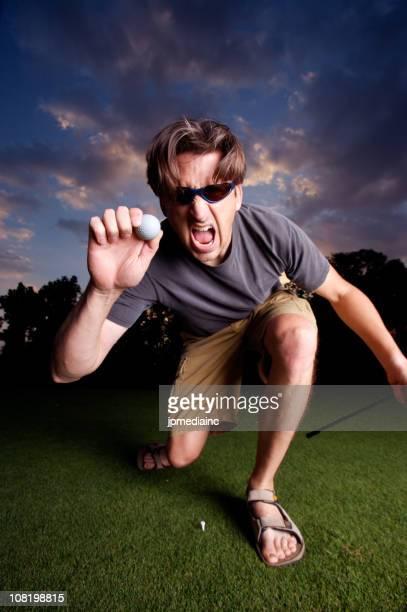 Homme tenant Balle de Golf