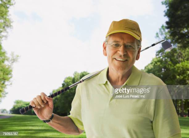 Man holding golf club on shoulder