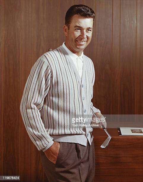 Man holding golf club, smiling