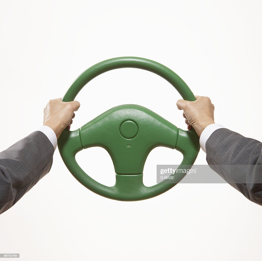 man holding  green steering wheel