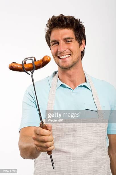 Man holding grilled sausage, smiling, portrait