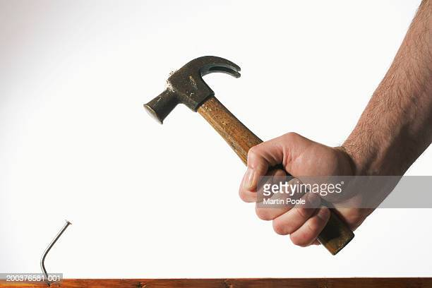 Man holding hammer by bent nail, close-up