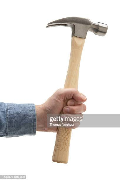 Man holding hammer, close-up of hand
