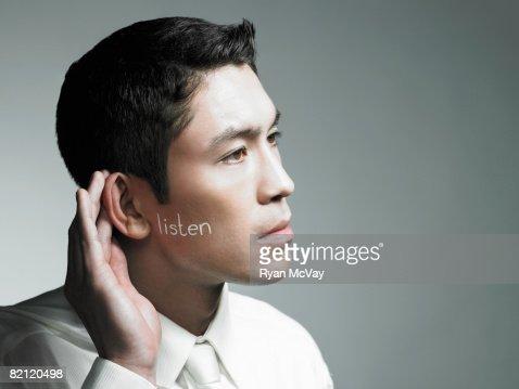 Hombre que agarra mano para los oídos