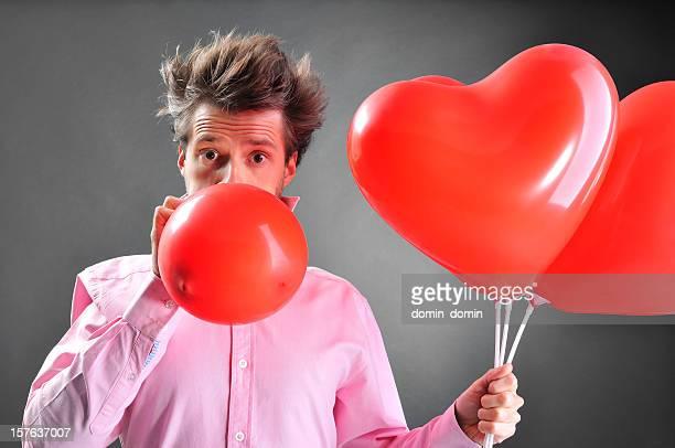 Mann hält herzförmige Ballons und er versucht zu übertreiben ein weiteres