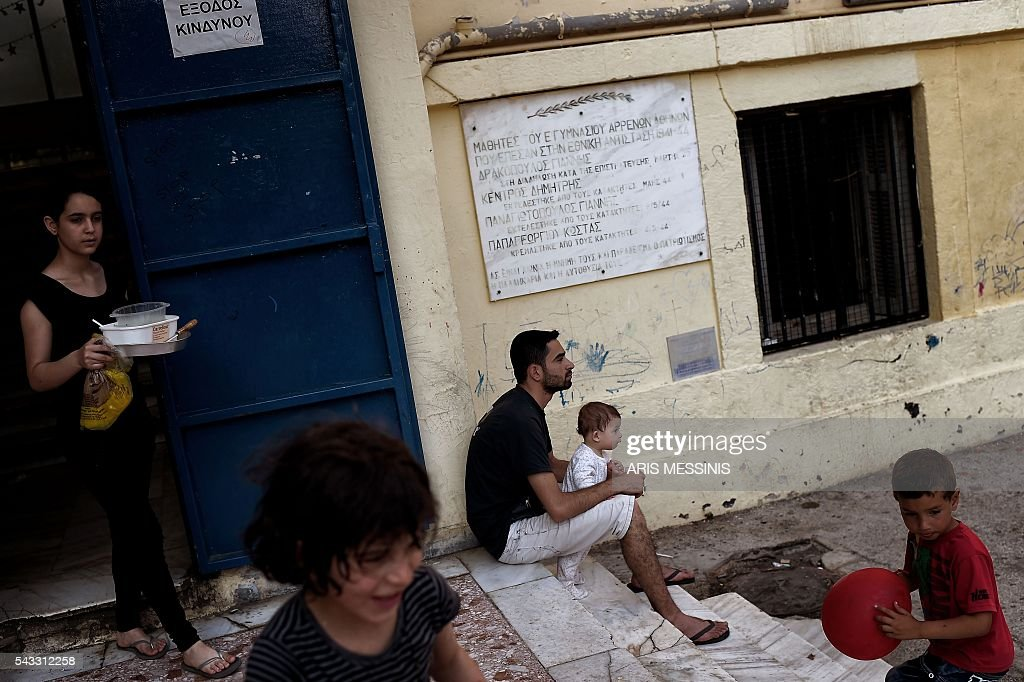 A man holding his baby sits at the yard of an abandoned school used by volunteers for hosting families of refugeees from Syria and Afghanistan in Athens on June 27, 2016. / AFP / ARIS