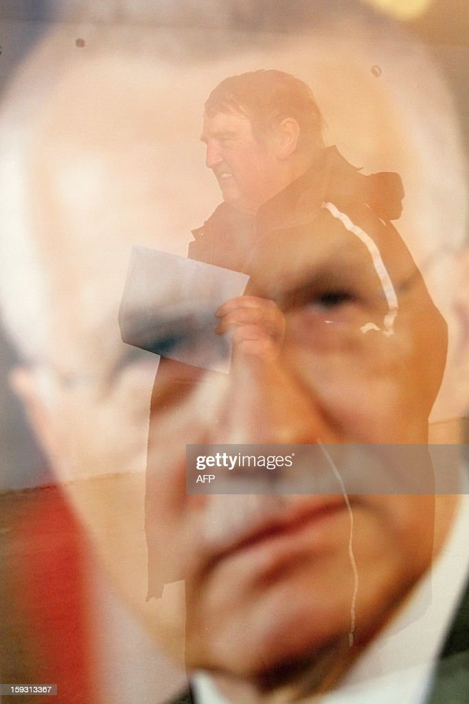 A man holding his ballot is reflected in a picture of Czech President Vaclav Klaus in Strani, Czech on January 11, 2013. Czech polling stations opened on January 11 afternoon in local mid-time for the first round of the first Czech direct presidential election in history.