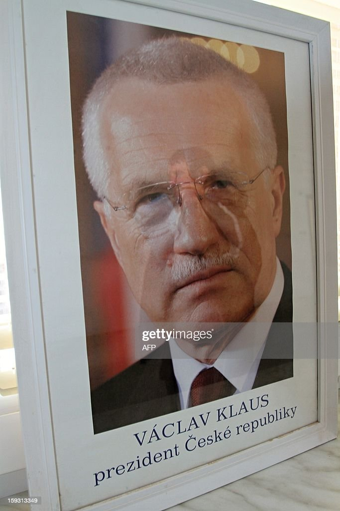 A man holding his ballot is reflected in a picture of President Vaclav Klaus in Strani, Czech on January, 2013. Czech polling stations opened on January 11 afternoon in local mid-time for the first round of the first Czech direct presidential election in history. AFP PHOTO / RADEK MICA