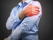 man holding his shoulder in pain