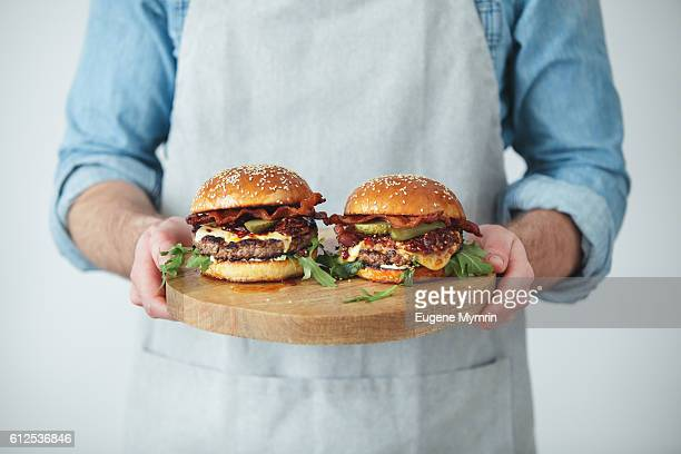 Man holding homemade angus beef burgers with bacon whisky jam