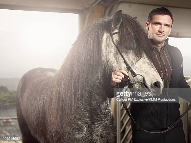 Man holding horse in stable