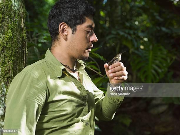 Man holding hummingbird on hand in jungle