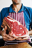 Man holding joint of beef at market stall, close-up of hands