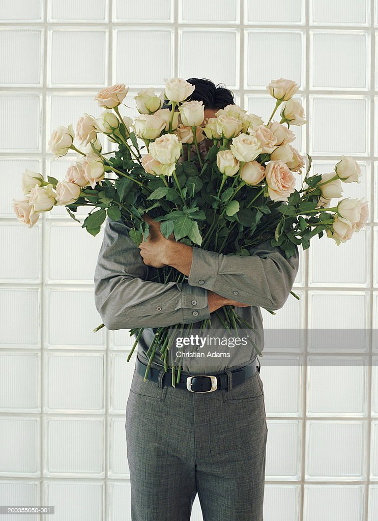 Man holding large bunch of white roses, face obscured : Stock Photo