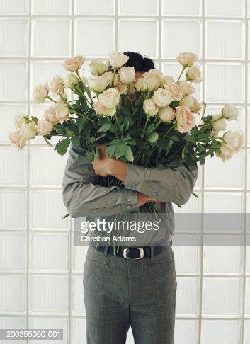 Man holding large bunch of white roses, face obscured : Bildbanksbilder