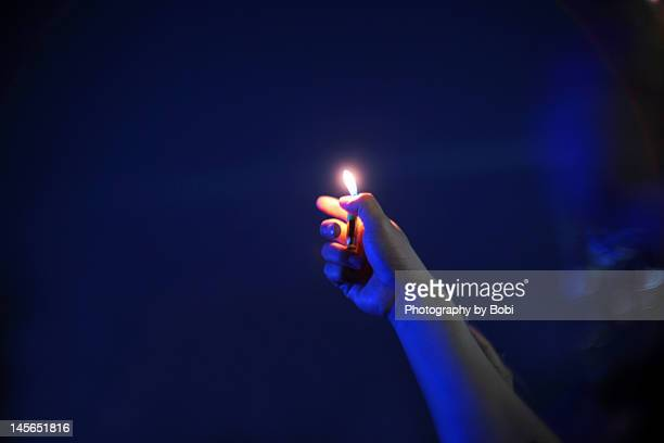 Man holding lighters in night