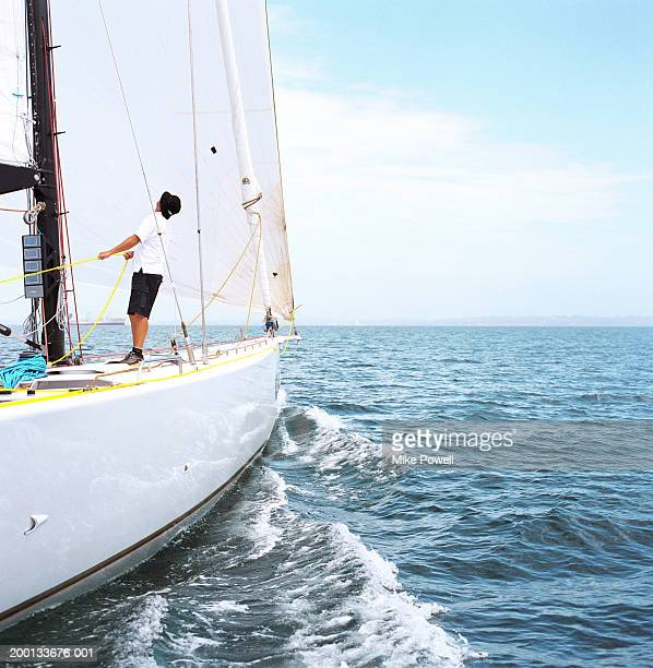 Man holding line of sailing ocean going racing yacht, looking upward