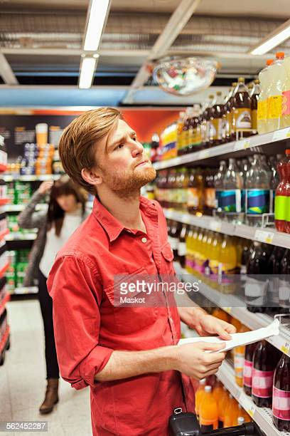 Man holding list while shopping in supermarket