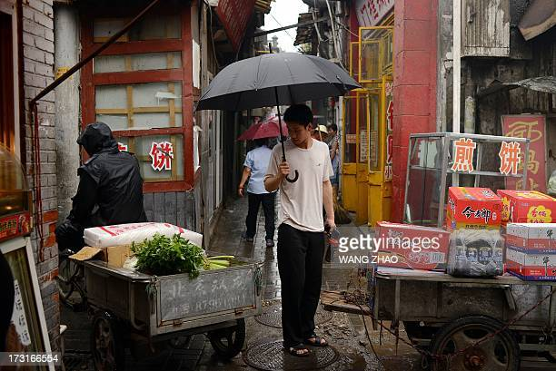 A man holding looks at a tricycle loaded with vegetables in an alley in Beijing on July 9 2013 China's annual inflation accelerated to 27 percent in...