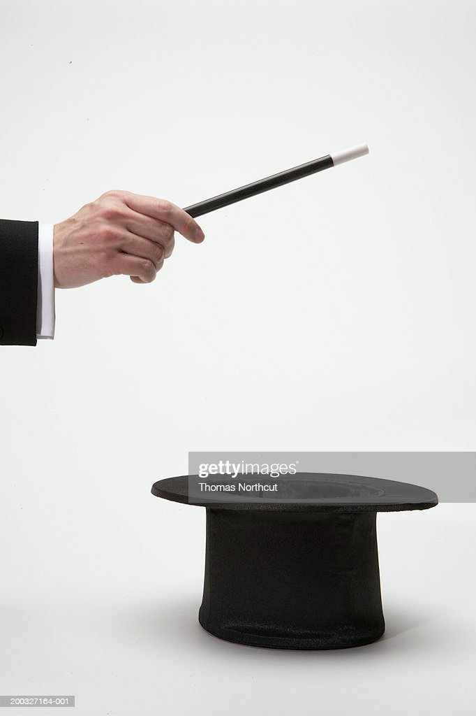 Man holding magic wand over top hat, close-up of hand, side view : Stock Photo