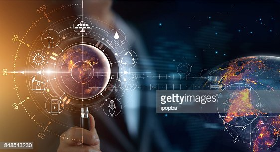Man holding magnifying glass, search earth with lights in the night of global show the world's consumption with icons energy sources for renewable, sustainable development. Ecology concept. Elements of this image furnished by NASA. : Stock Photo