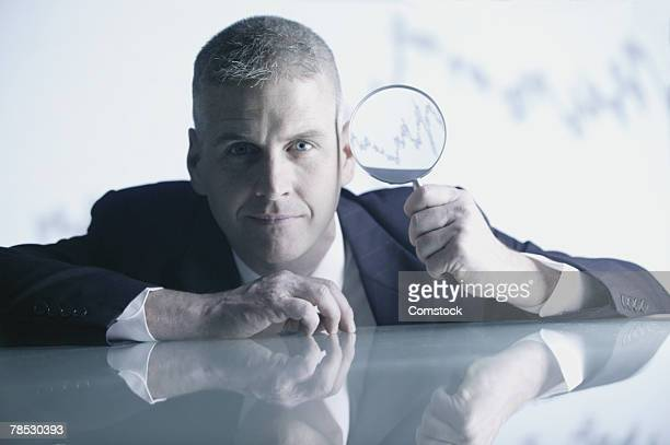 Man holding magnifying glass with graph