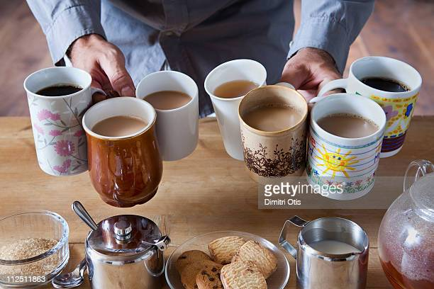 Man holding many tea and coffee cups