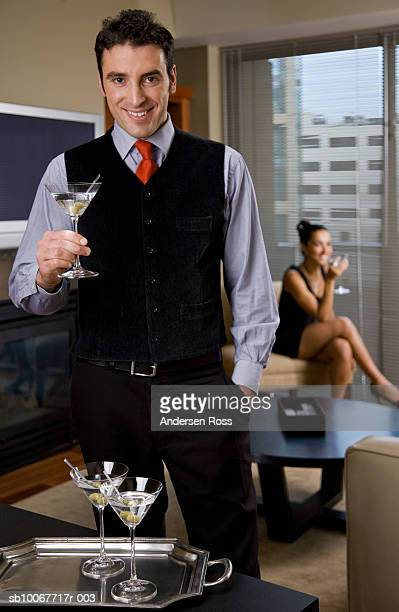 Man holding martini glass, woman in background