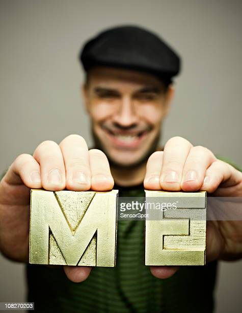 man holding me block letters