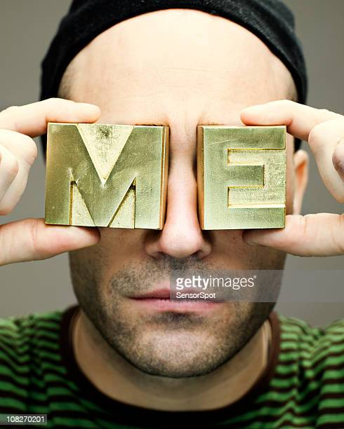 man holding 'me' block letters to face
