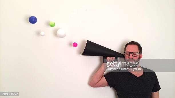 Man Holding Megaphone With Balls Emerging Against White Wall