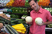 Man holding melons against chest, smiling, portrait, close-up
