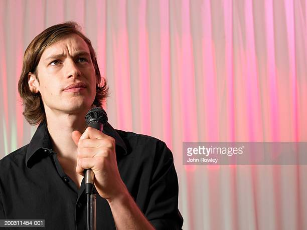 Man holding microphone, frowning