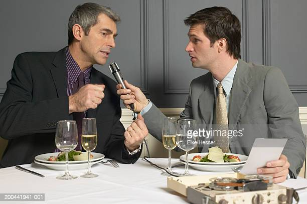 Man holding microphone interviewing businessman in restaurant