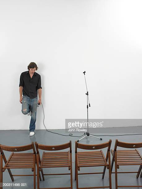 Man holding microphone, leaning against wall in front of empty chairs