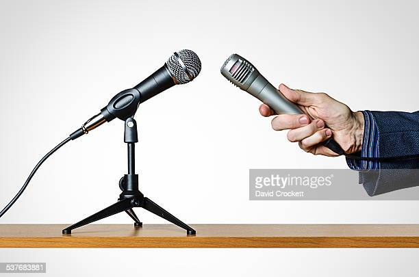 Man holding microphone up to another microphone