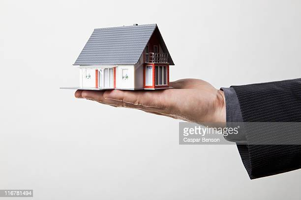 Man holding miniature home in the palm of his hand