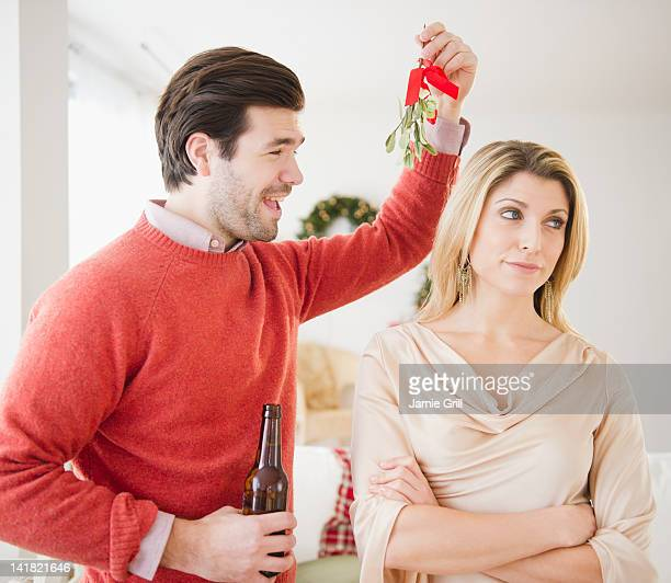 Man holding mistletoe over displeased woman