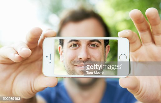man holding mobile with selfie on screen