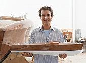 Man holding model boat in boat building workshop, smiling, portrait