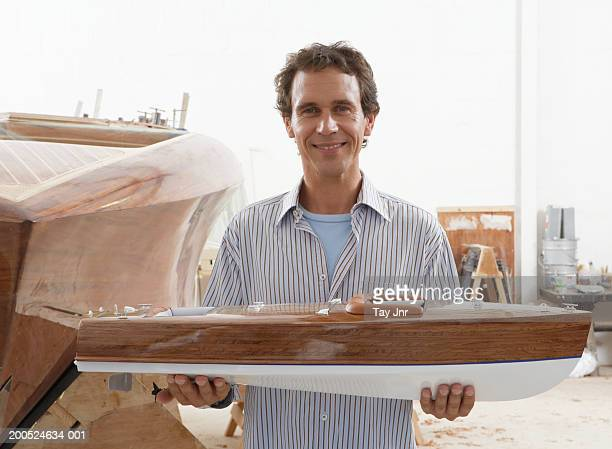 Man holding model boat in boat building workshop, smiling, portrait