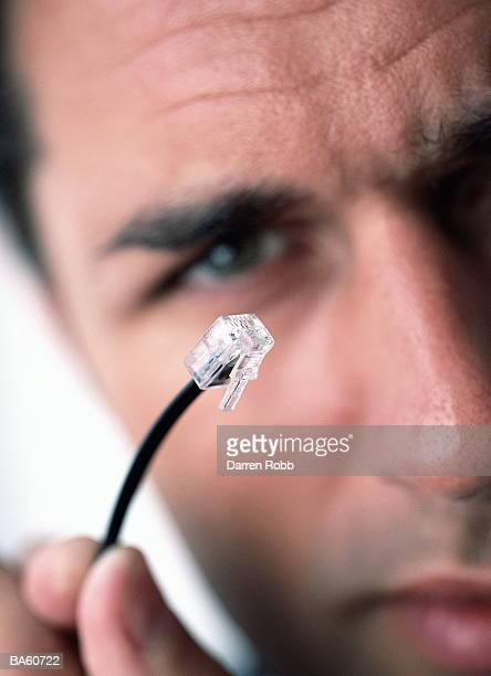 Man holding modem plug, close-up