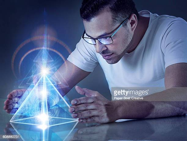 Man holding modern pyramid projection with lasers