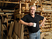 Man holding mug by planks of wood on shelves, smiling, portrait