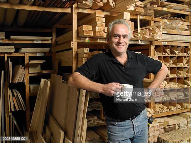 Man holding mug by planks of wood on shelves, smiling, portrait