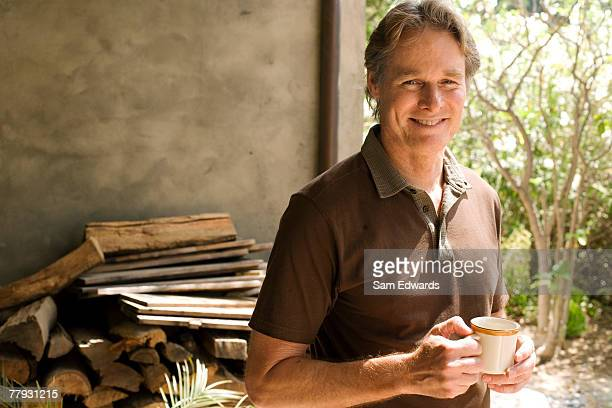 Man holding mug in front of wood pile and shed