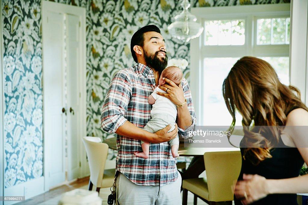 Man holding newborn baby for friend in kitchen : Stock Photo