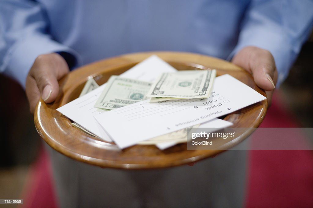 Man holding offering plate, close-up : Stock Photo